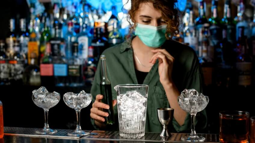 bartender girl in medical mask preparing to make cocktail.