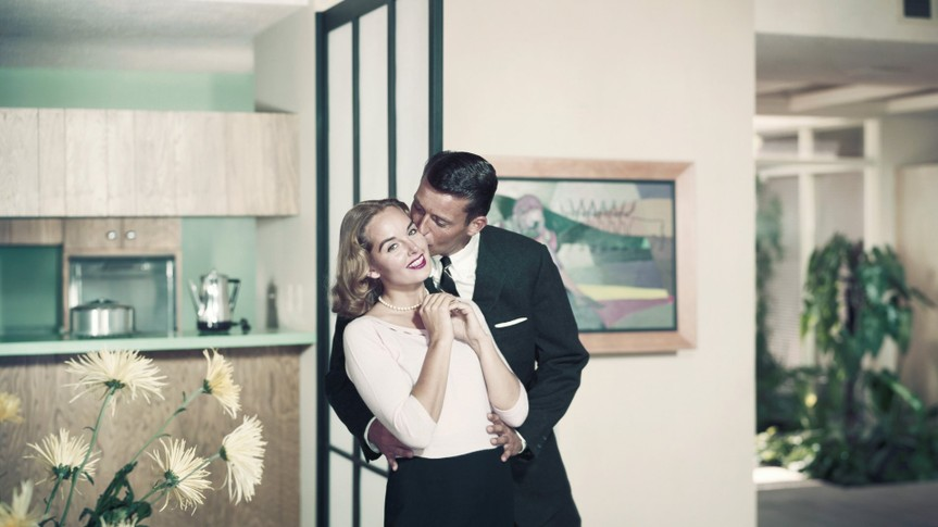 1966, Two People, Adults Only, Young Adult, Young Women, Mid Adult, Mid Adult Men, Caucasian Appearance, Indoors, Horizontal, Colour, Photography, Three Quarter Length, Focus On Foreground, Full Suit, Smart, Casual, Blonde Hair, Standing, Kissing, Looking At Camera, Toothy Smile, Cheerful, Hand On Hip, Flower, Living Room, Heterosexual Couple, Togetherness, Happiness, Love, Bonding, Romance, 1966