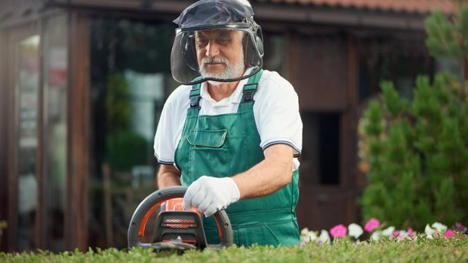 Front view of eldery man landscaping and taking care of plants in garden.