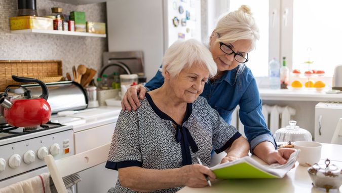 Mature woman helping elderly mother with paperwork.