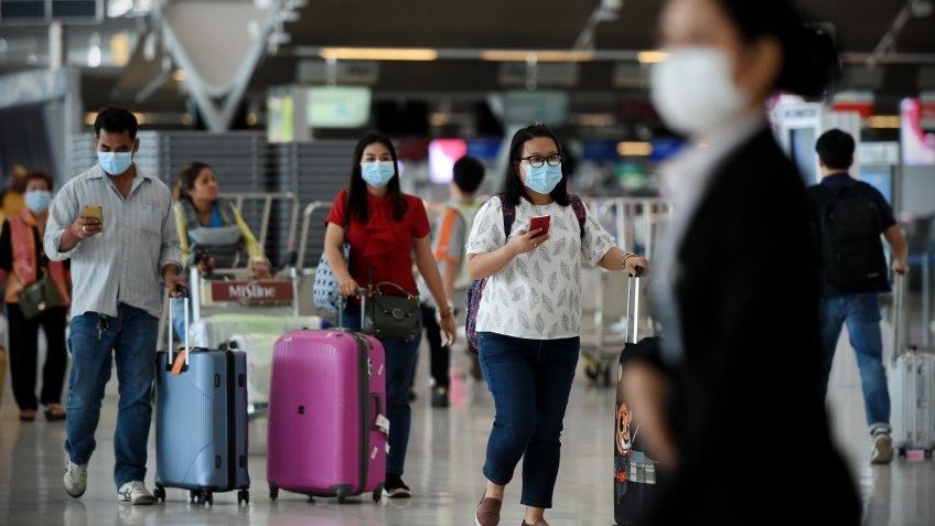 Bangkok, Thailand - February 18, 2020: Air travelers wearing masks walk through departures hall of Suvarnabhumi Airport.