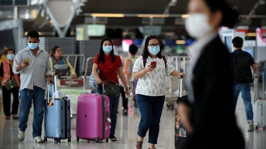 Bangkok, Thailand - February 18, 2020: Air travelers wearing masks walk through departures hall of Suvarnabhumi Airport.