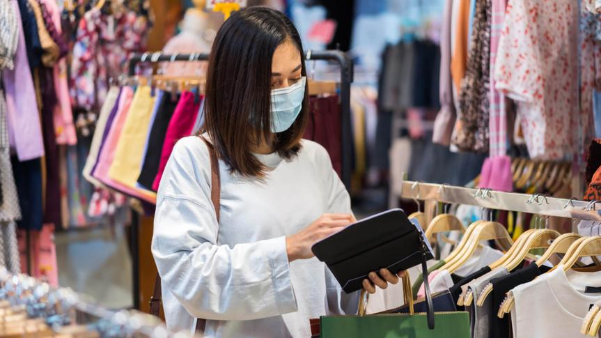 young woman open purse to payment for clothes at shopping store and her wearing medical mask for prevention from coronavirus (Covid-19) pandemic.