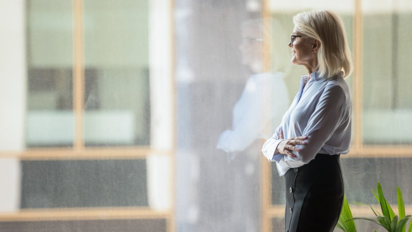 Smiling confident mature businesswoman pondering strategy, standing near big window in modern office, looking at cityscape, entrepreneur lost in thoughts, planning future project, business vision.