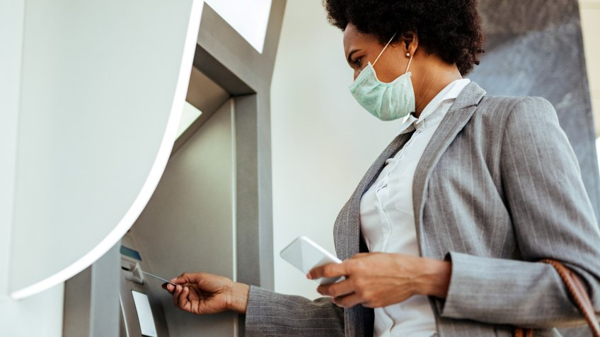 Low angle view of African American businesswoman inserting credit card and withdrawing cash at ATM  while wearing protective mask on her face.