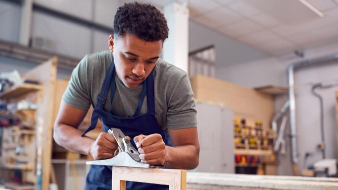 Male Student Studying For Carpentry Apprenticeship At College Using Wood Plane.
