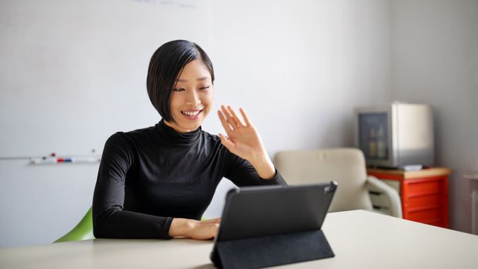 Businesswoman working in office, doing a video call with digital tablet.