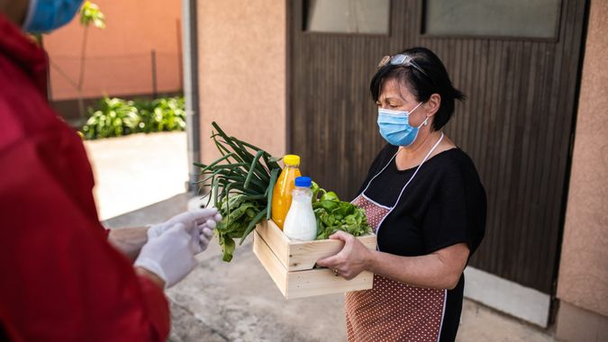 Senior woman wearing protective mask taking groceries from caring volunteer during covid-19 lockdown.