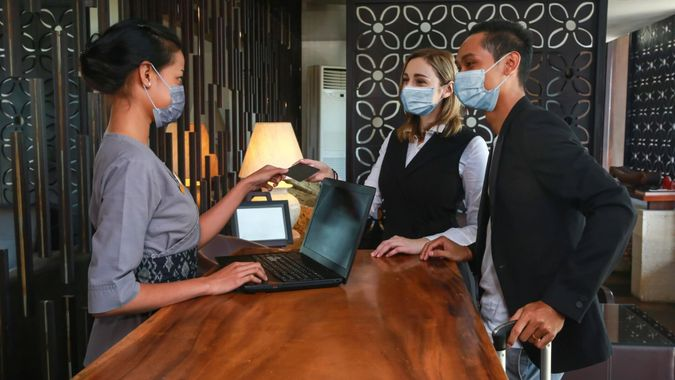 Couple and receptionist at counter in hotel wearing medical masks as precaution against virus.