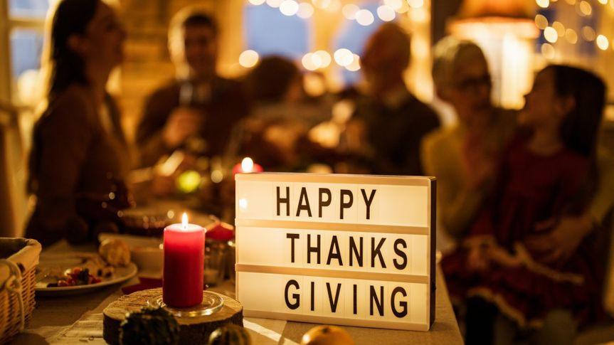Close up of a candle and sign with 'Happy Thanksgiving' on dining table with people in the background.