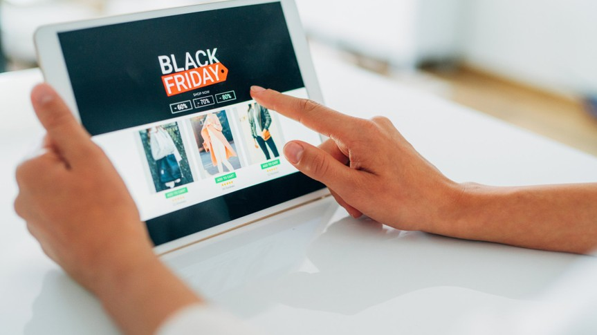 Close-up shot of a young woman holding a digital tablet and shopping online on Black Friday at home.