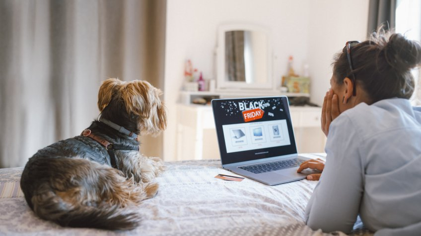 Woman is buying electronics online at Black Friday while relaxing at the bed with her dog.