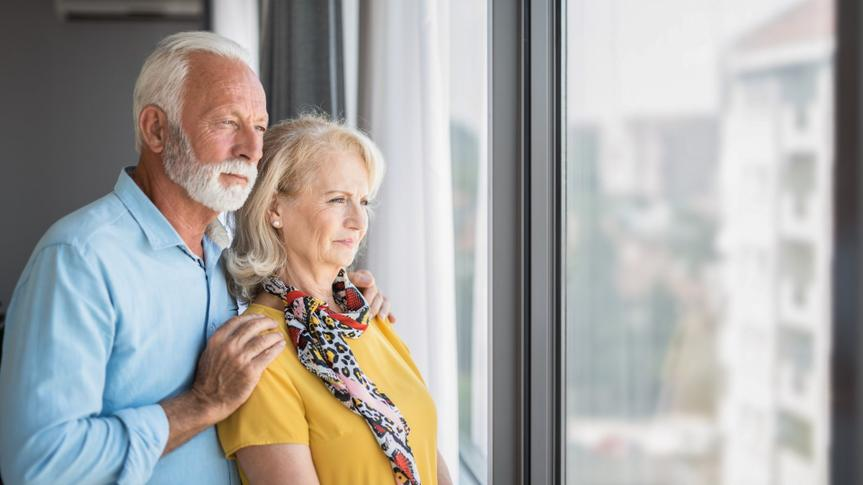 Worried senior couple looking at view through window of their home.