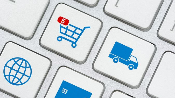 Online shopping / ecommerce and retail sale concept : Shopping cart, delivery van, credit card, world globe logo on a laptop keyboard, depicts customers order things from retailer sites using internet.