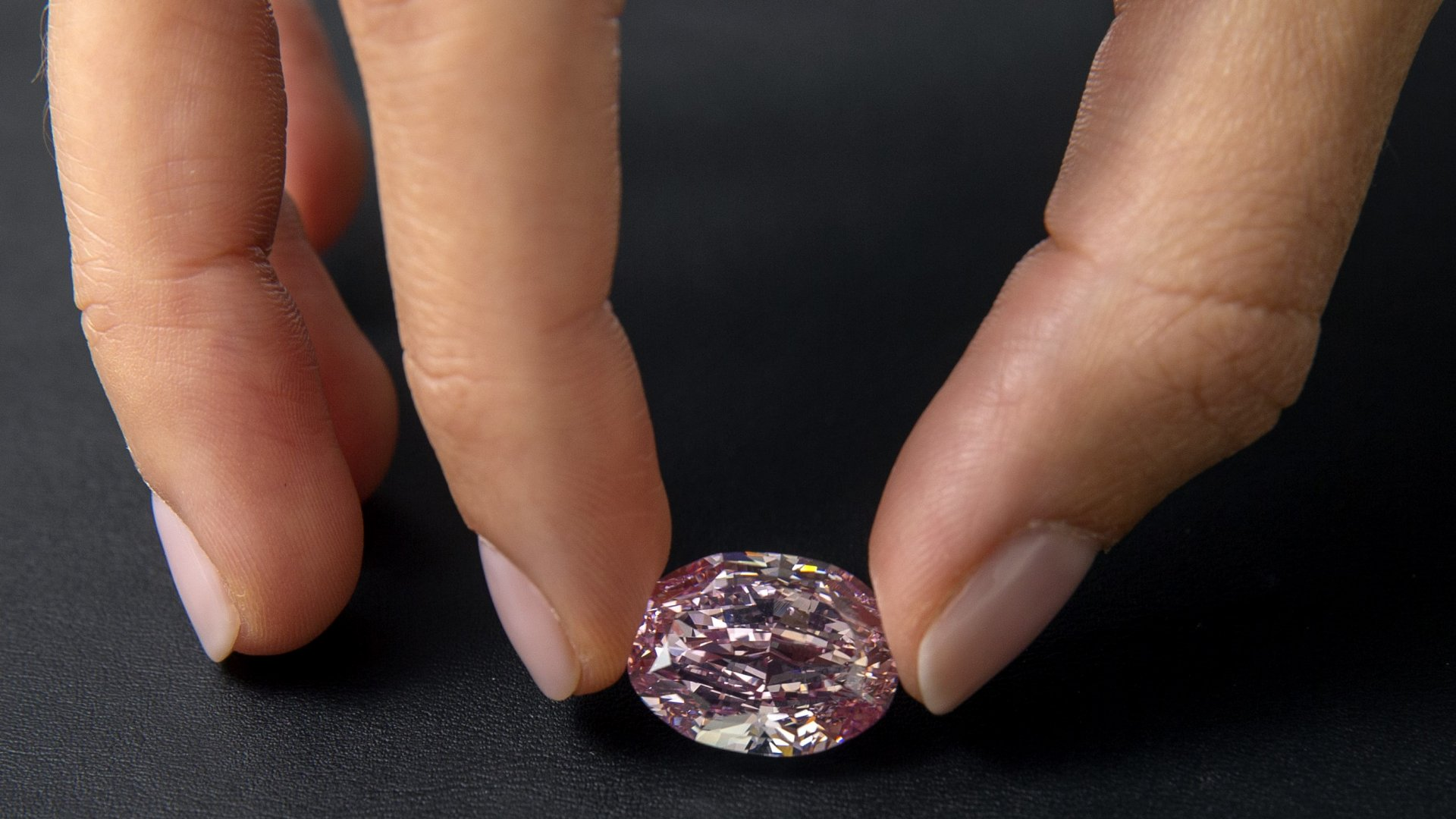 Mandatory Credit: Photo by SALVATORE DI NOLFI/EPA-EFE/Shutterstock (11005295e)A Sotheby's employee poses with 'The Spirit of the Rose' vivid purple-pink diamond weighing 14.
