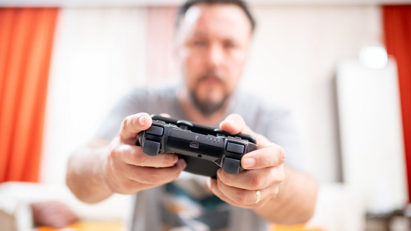 man holding game controller playing video games