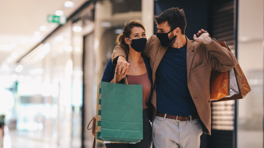 The young couple carries shopping bags and walks through the mall, wearing protective masks, life in a time of pandemic.