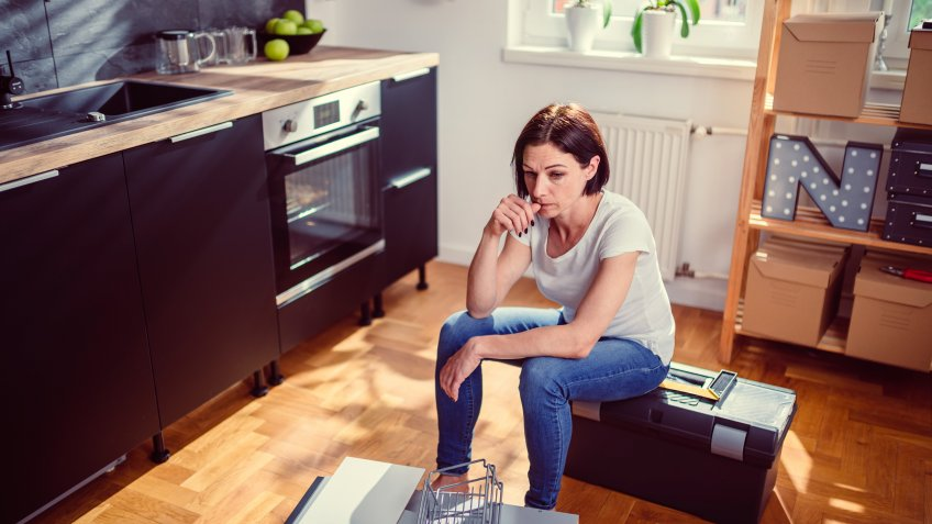 Worried woman sitting on a toolbox during renovating kitchen.