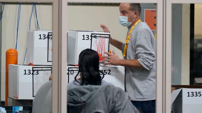 Mandatory Credit: Photo by John Locher/AP/Shutterstock (11002197e)County election worker moves boxes of mail-in ballots at a tabulating area at the Clark County Election Department, in Las VegasElection 2020 Nevada Vote Counting, Las Vegas, United States - 05 Nov 2020.