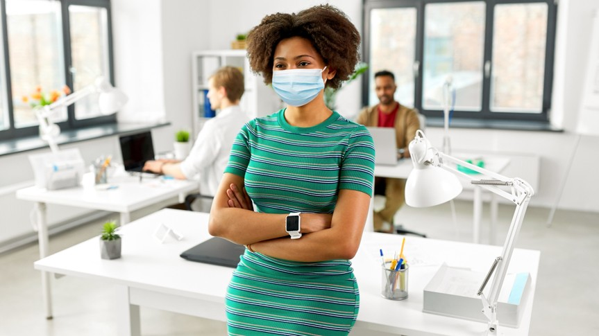 Woman with smart watch in medical mask at office stock photo