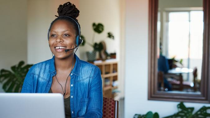 Shot of a young woman using a laptop and headset while working from home.