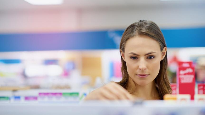A young woman buying medicine in a pharmacy -The commercial designs displayed in this image represent a simulation of a real product and have been changed or altered enough by our team of retouching and design specialists so that they are free of any copyright infringementshttp://195.