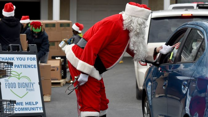 Mandatory Credit: Photo by Aimee Dilger/SOPA Images/Shutterstock (11566852a)A Santa hands candy canes to a guest at the Al Beech food pantry.