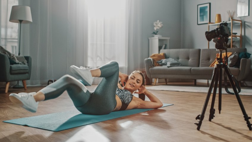 Beautiful Athletic Female Fitness Blogger is Talking on Camera and Recording her Crisscross Crunch Workout Routine in a Spacious and Bright Living Room with Cozy Modern Interior.