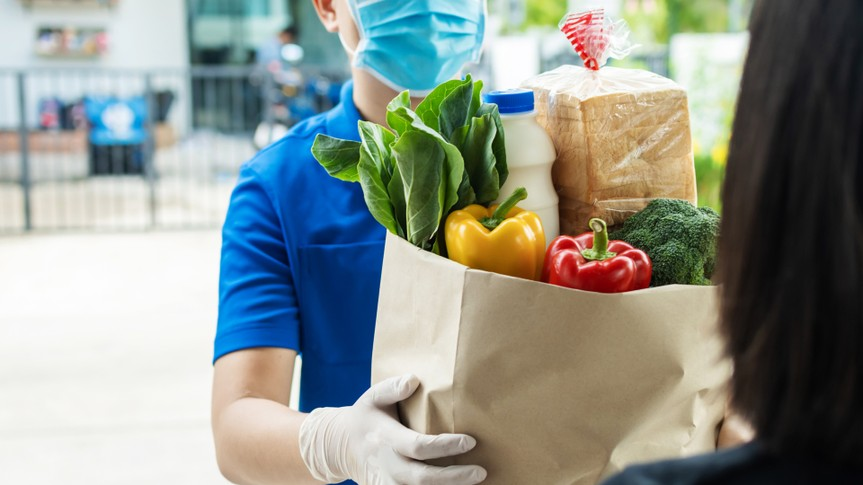 hand of food delivery service man wearing protection face mask holding fresh food set paper bag to customer at door home, express delivery, new normal, virus outbreak, takeaway food delivery concept