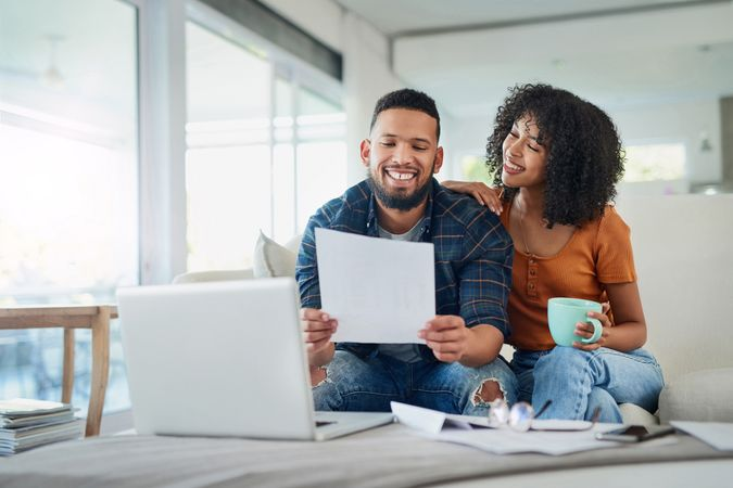 Shot of a happy young couple looking going over their finances at home.