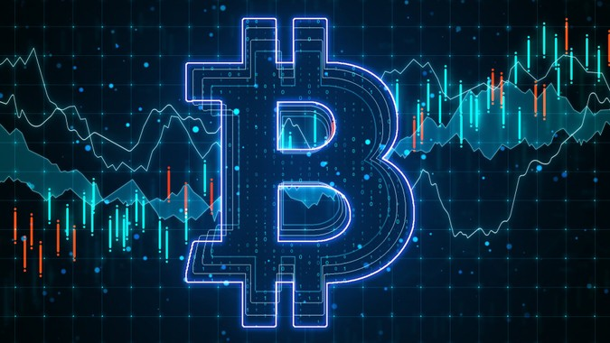 E-commerce concept with big glowing bitcoin circuit at business statistic graphs background.