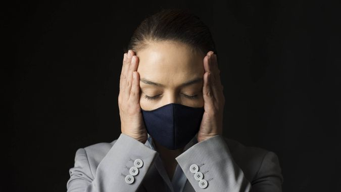 Caucasian female with protective face mask and eyes closed in front of black background is holding her head with her hands.