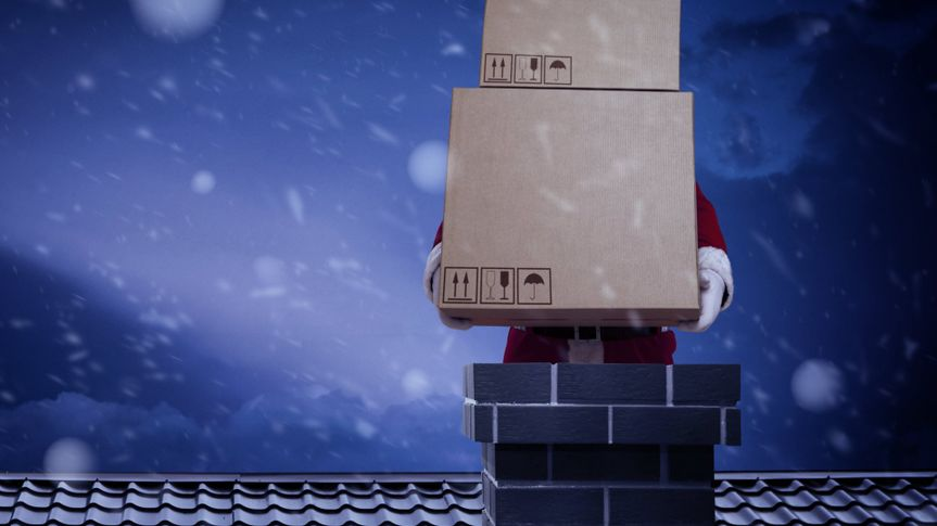Santa Claus on roof with big boxes.