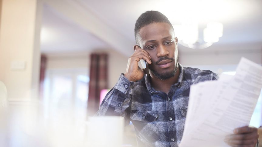 Young black male on the phone in a home environment holding paperwork.
