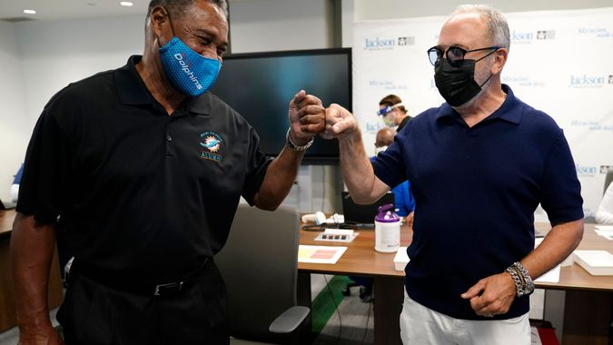 Mandatory Credit: Photo by Lynne Sladky/AP/Shutterstock (11674612a)Former Miami Dolphins football player Nat Moore, 69, left, bumps fists with music producer Emilio Estefan, 67, right, before receiving the Pfizer-BioNTech COVID-19 vaccine at Jackson Memorial Hospital, in Miami.