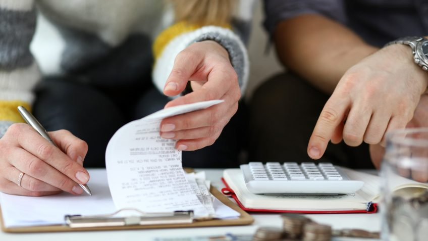 Close-up view of man and woman making account of family income.
