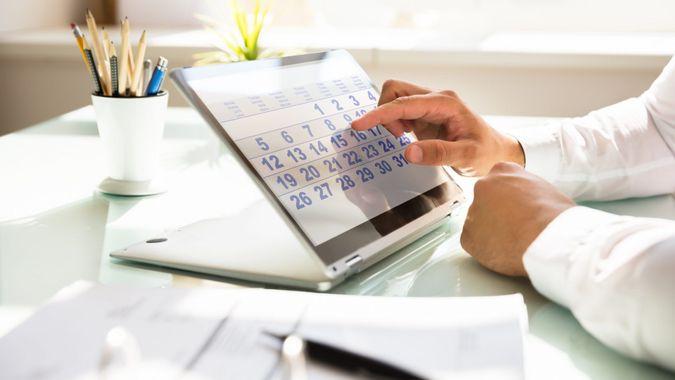 Close-up of a businessman's hand using calendar on laptop over desk.