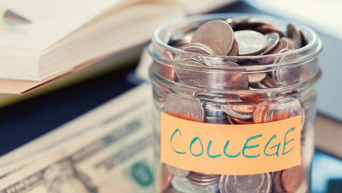 """Glass jar full of US coins and a """"COLLEGE"""" label on a table with books and paper currency."""