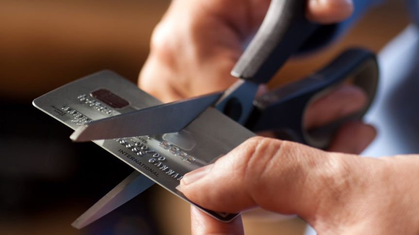 Male hands cutting a credit card with scissors.