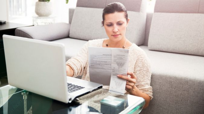 Woman in her 30s filling out tax information online.