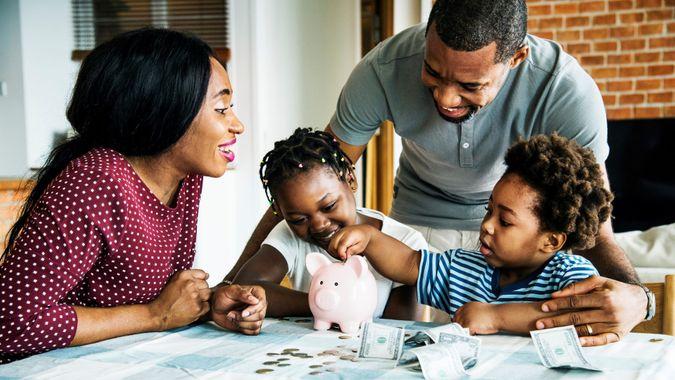Family saving money to piggy bank.