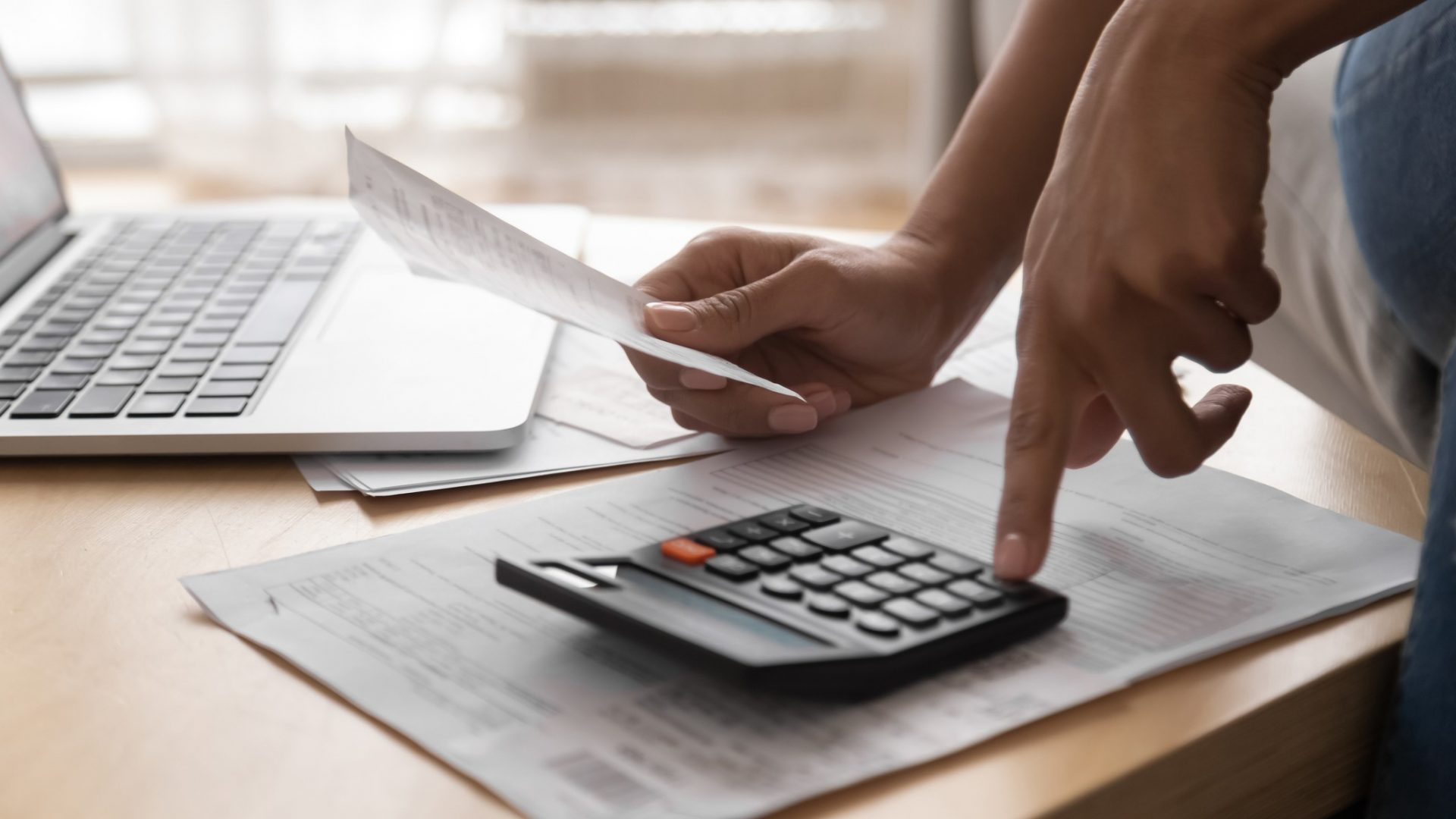 African woman holding in hand paper bills bank receipt using calculator on table calculate debt loan tax cost to pay manage finances concept doing accounting paperwork budget analysis, close up view.