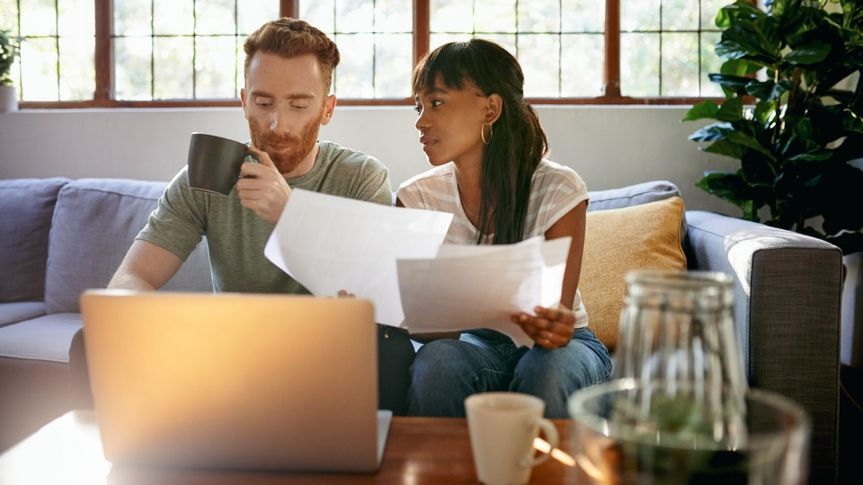 Shot of a young couple going through paperwork while using a laptop at home.