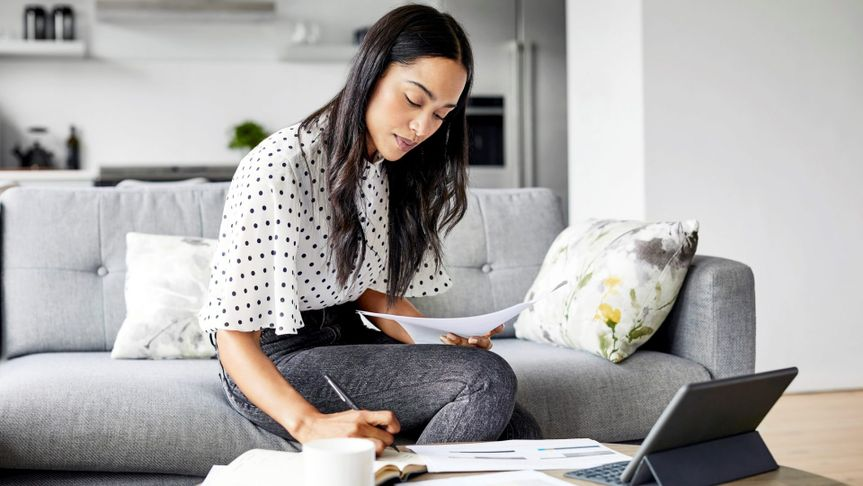 Young woman analyzing bills while writing in diary.