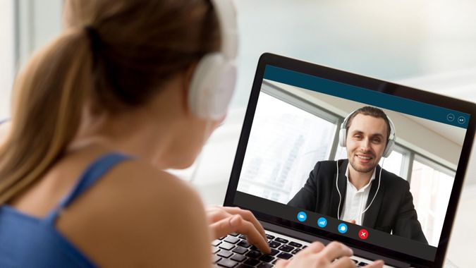 Man and woman in headphones communicating online by video call, looking at full screen videoconferencing app window, webcam videochat, virtual dating, long distance relationships, close up rear view.