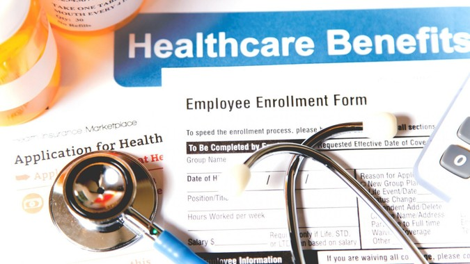 Healthcare benefit forms including: enrollment forms and applications, stethoscope, calculator.