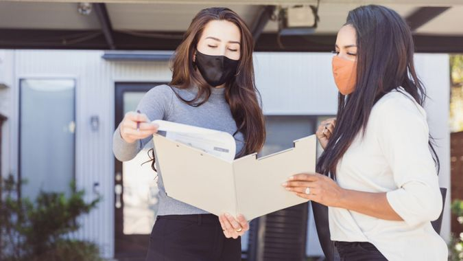 A confident young adult female real estate agent review contract terms and conditions with a home buyer.