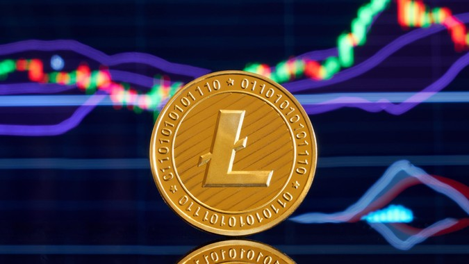 Gold coin litecoin on a bright background of business graphics close-up.