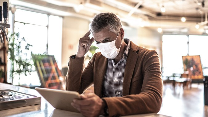 Mature businessman with mask using digital tablet at work.