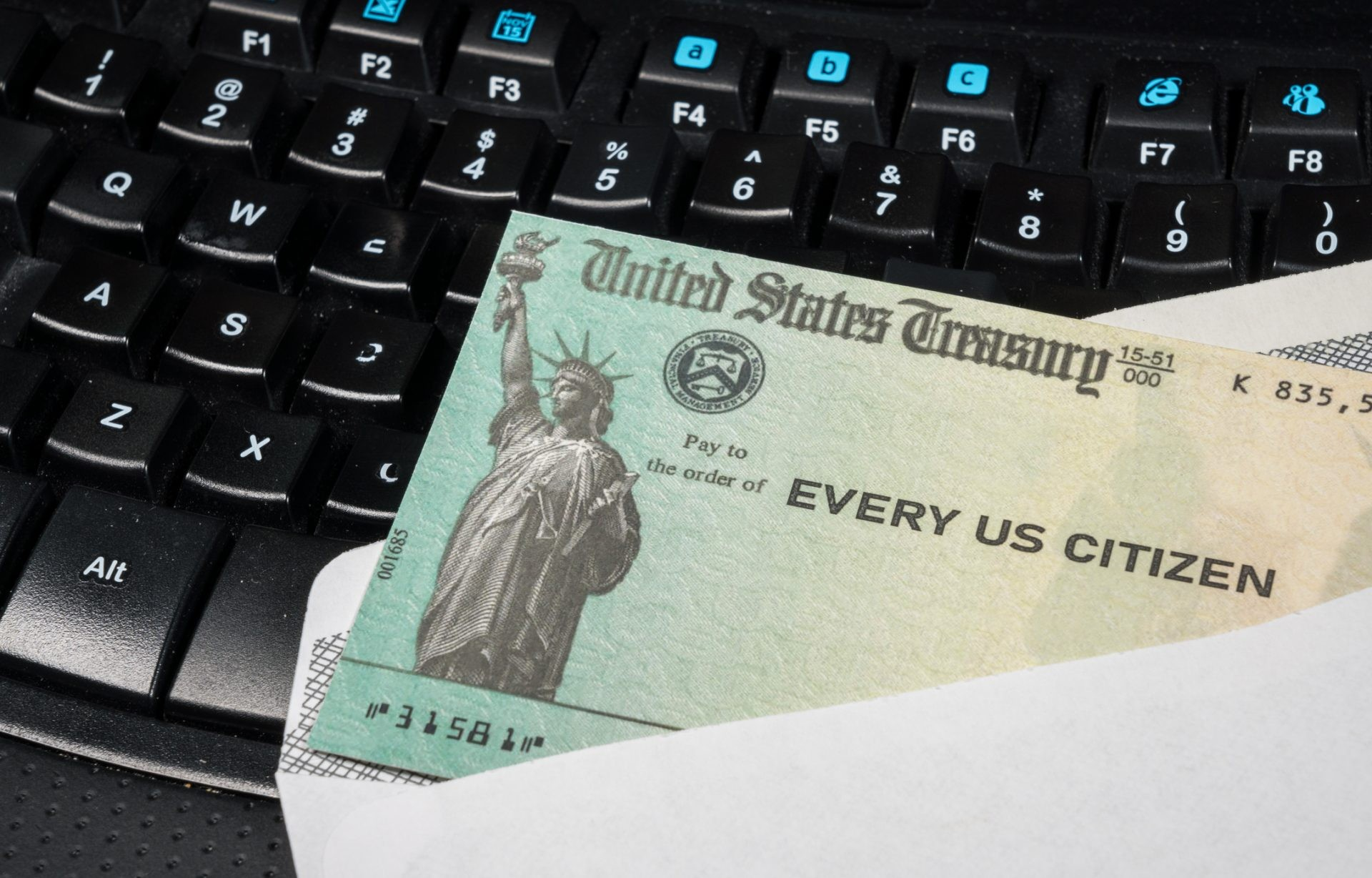 US Treasury concept check to illustrate coronavirus stimulus payment on keyboard used for working from home.